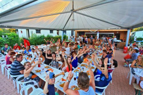 Personnes joyeuses lors d'une soirée paëlla sur la terrasse du bar / snack du camping.