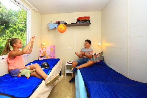 Mobil Home O'hara Grand Confort, chambre pour enfants avec lits simples côte à côte.